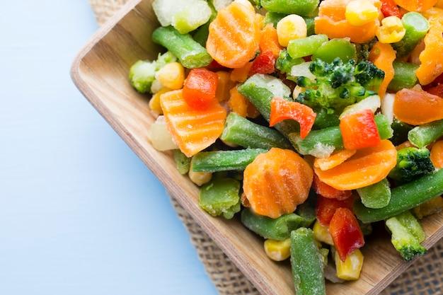 Verdura congelata in un piatto di legno
