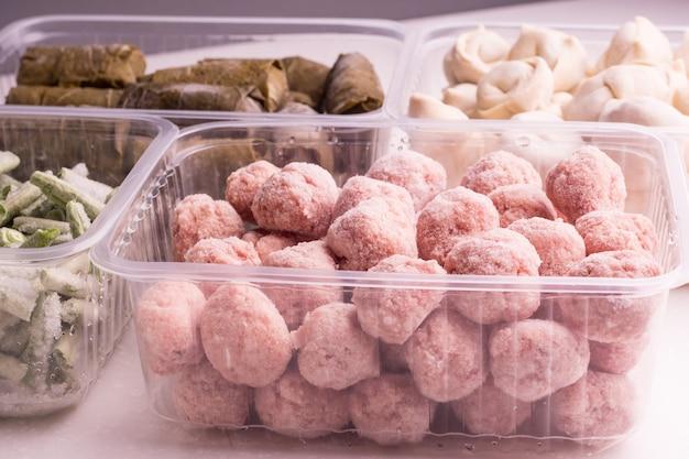 Verdure surgelate e prodotti a base di carne semilavorati in contenitori di plastica su un piatto bianco. polpette, canederli, dolma in foglie di vite, fagioli tritati