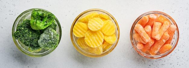 Verdure congelate come broccoli verdi, carote gialle e baby in ciotole di vetro su ghiaccio e sfondo grigio cemento con spazio di copia. bandiera.