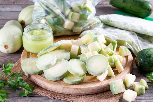 Zucchine surgelate. verdure surgelate sul tavolo di legno. concetto di cibo congelato