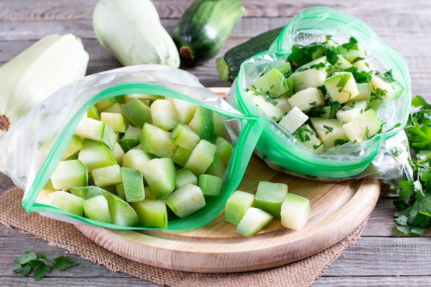 Zucchine congelate in un sacchetto di plastica su un tavolo di legno. concetto di cibo congelato