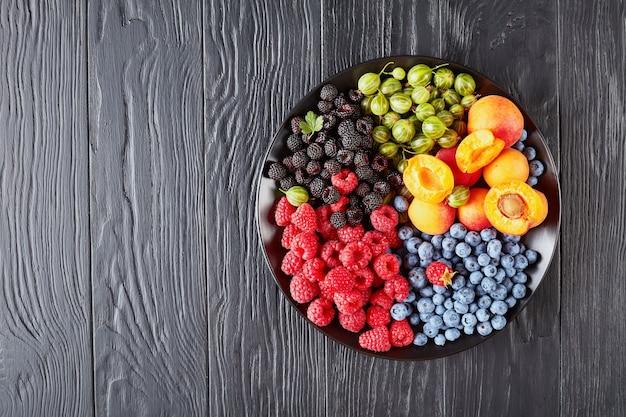 Piatto di frutta e bacche con uva spina fresca biologica, lampone rosso e nero, mirtillo, fette di albicocca su un tavolo di legno nero, vista orizzontale dall'alto, spazio di copia