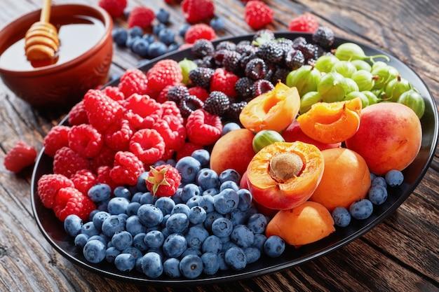 Insalata di frutta e bacche con uva spina biologica fresca, lampone rosso e nero, mirtillo, fette di albicocca su una piastra nera su una tavola in legno rustico con miele nella ciotola, vista da sopra,