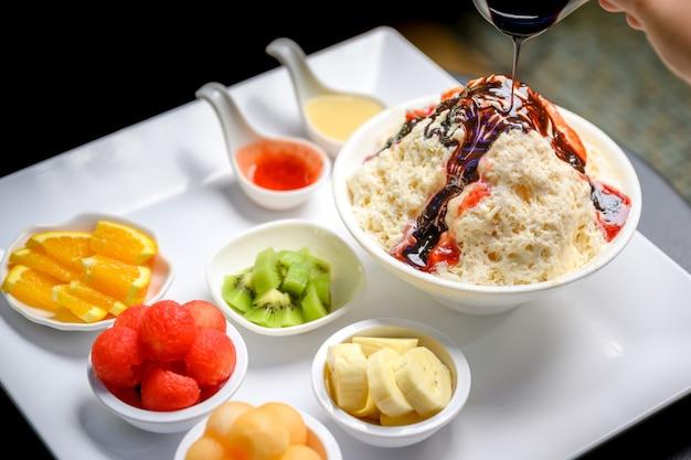 Bingsu di frutta o ghiaccio tritato condito con condimenti il ghiaccio tritato coreano di fiocchi di neve (bingsu di frutta mista) è il dolce nazionale della corea. cibo dolce popolare in corea in estate.
