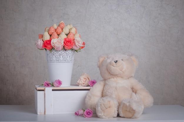 Decorazione di bouquet di frutta con orsacchiotto di peluche sul tavolo