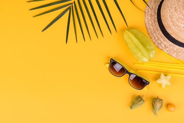 Carambola di frutta, accessori da spiaggia e fogliame di una pianta tropicale su carta colorata. sfondo estivo con stelle marine e frutti
