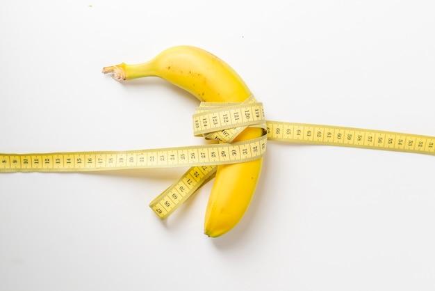 Nastro di frutta e centimetri su superficie bianca. concetto di dieta