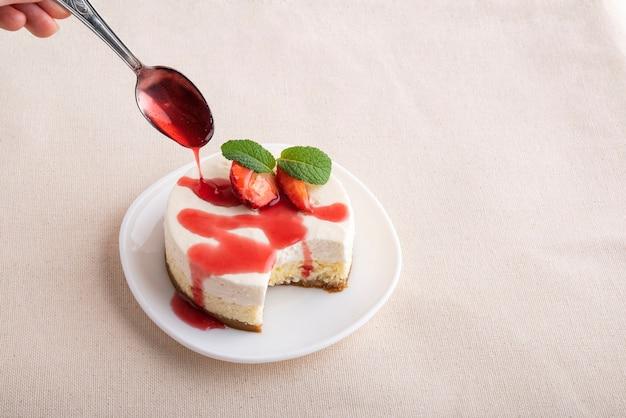 Cheesecake alla frutta, con fragole fresche e succo di frutti di bosco. dessert classico.