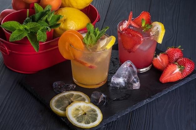 Cocktail di frutta con frutta fresca e ghiaccio. in bicchieri su fondo rustico in legno nero