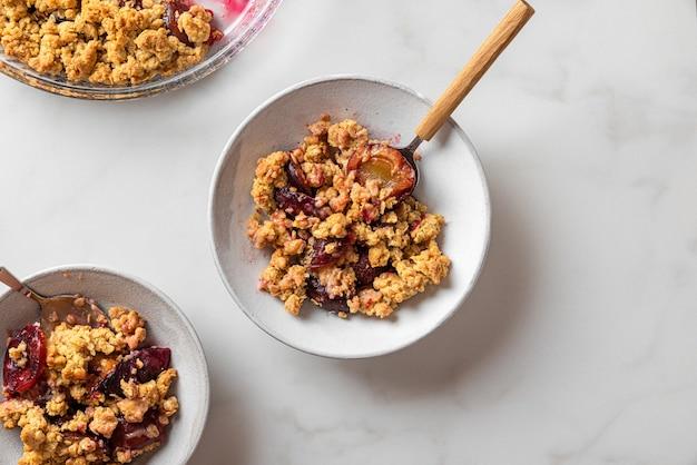 Sbriciolata di frutta. torta sbriciolata di prugne in piatti con cucchiai sul tavolo di marmo bianco per una gustosa colazione. vista dall'alto con copia spazio