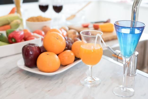 Succo di frutta e frutta sul bancone di marmo nella cucina