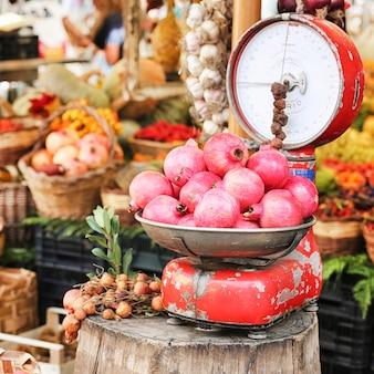 Mercato della frutta con bilance antiche e granato a campo di fiori