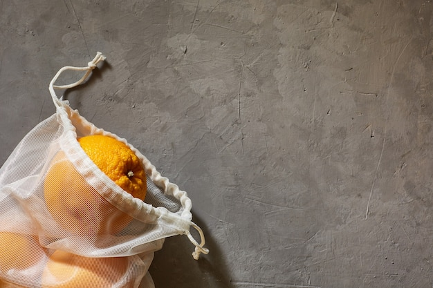 Arance alla frutta in eco bag con retina bianca su fondo grigio. copyspace.