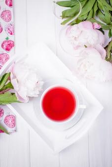Il tè rosso della frutta e l'estate fioriscono le peonie su legno bianco