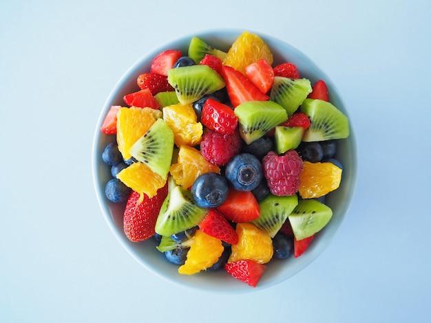 Macedonia di frutta in una ciotola sulla superficie blu