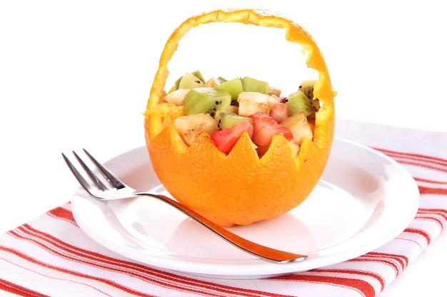 Macedonia di frutta in arancia scavata isolata su bianco