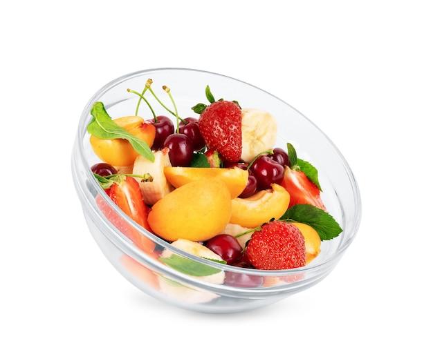 Macedonia di frutta in un piatto trasparente su sfondo bianco