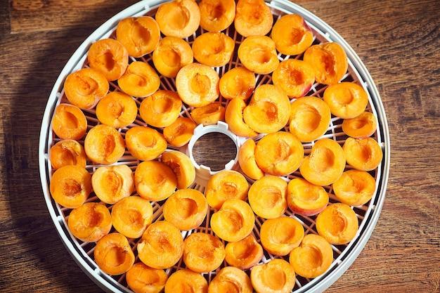 Fette di frutta su un disidratatore alimentare in plastica con profondità di campo ridotta