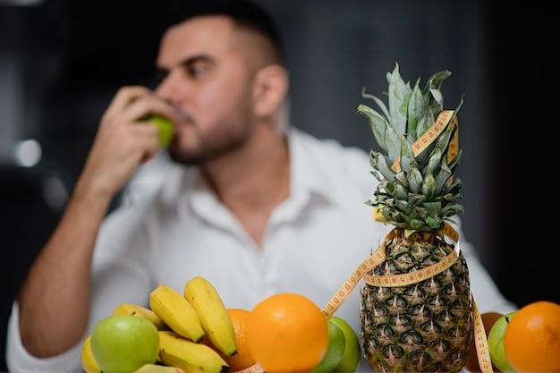Fruttifichi sul primo piano della tavola con un uomo nei precedenti. il concetto di uno stile di vita sano
