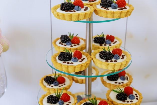 Mini dessert di crostate di frutta su supporto a più livelli in acrilico. avvicinamento.