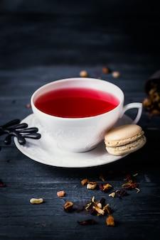 Macaron crema di tè e caffè alla frutta sul tavolo scuro