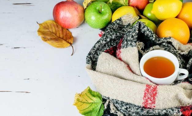 Tazza da tè alla frutta, sciarpa calda, agrumi tropicali come simboli del rimedio antivirus, potenziamento del sistema immunitario