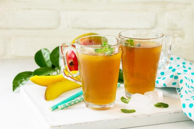 Tazze di tè alla frutta mango freddo del tè con la menta sulla tavola bianca rustica copia spazio