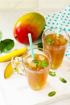 Tazze da tè alla frutta mango freddo alla menta su tavola bianca rustica