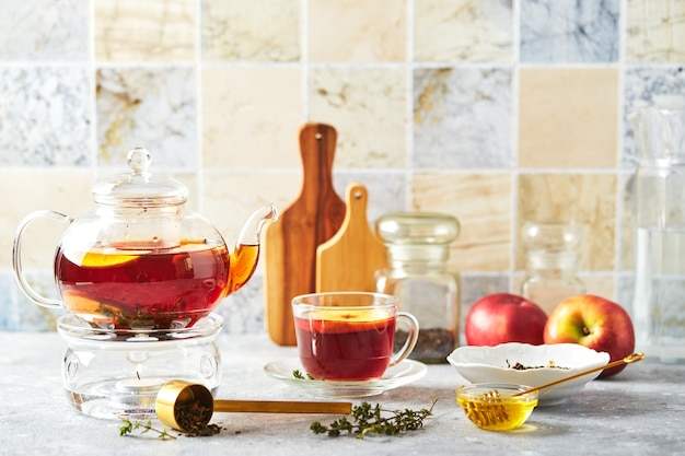 Tè alla frutta con mele e timo in teiera di vetro e tazza sul tavolo della cucina