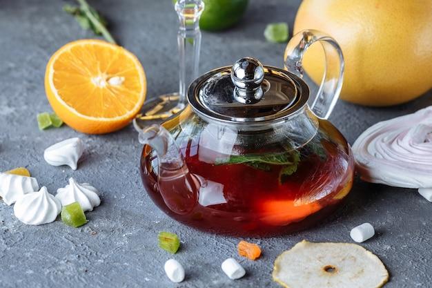 Tè alla frutta con menta, arance e mirtilli rossi su uno sfondo decorativo. bevande calde invernali.