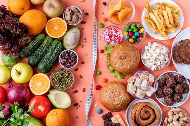 Frutta e verdura vs dolci e fast food vista dall'alto piatto giaceva su sfondo arancione