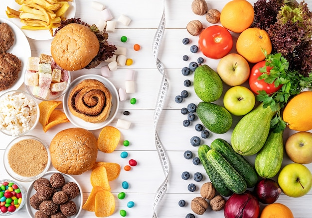 Frutta e verdura vs dolci e fast food vista dall'alto piatto laici