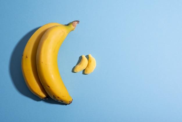 Frutta contro il concetto di caramelle con banane in pianura blu