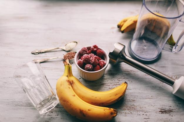 Frutta e frullatore per preparare frullati e ingredienti su uno sfondo chiaro, vista dall'alto