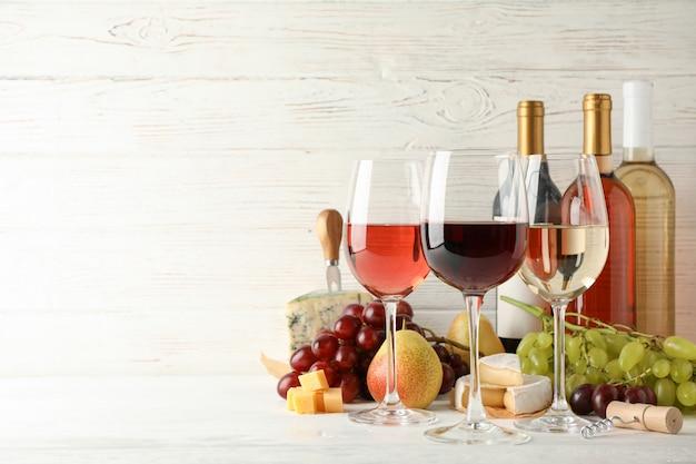 Frutta, formaggio, bottiglie e bicchieri con vino diverso su bianco