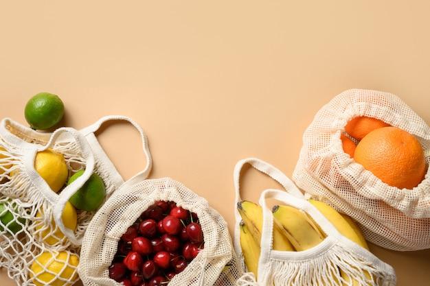Frutta e articoli citrici in borse ecologiche a rete su fondo beige. shopping senza sprechi.
