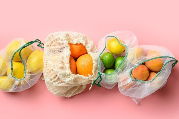Frutta e citazioni in sacchetti riutilizzabili ecologici in rete su sfondo rosa. shopping senza sprechi.