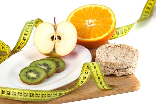 Frutta, uova, arancia, succo di mela sulla tavola di legno con misurazione isolata su bianco