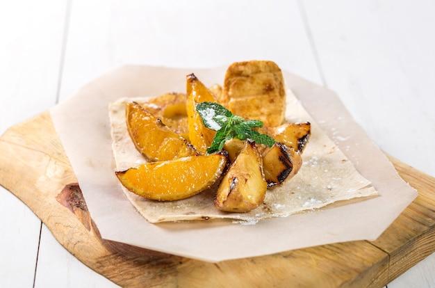 Frutta grigliata con menta da vicino su una tavola di legno sul tavolo
