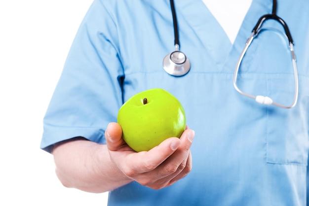 La frutta ti fa stare bene. primo piano del chirurgo in uniforme blu che tiene mela verde mentre sta in piedi isolato su bianco