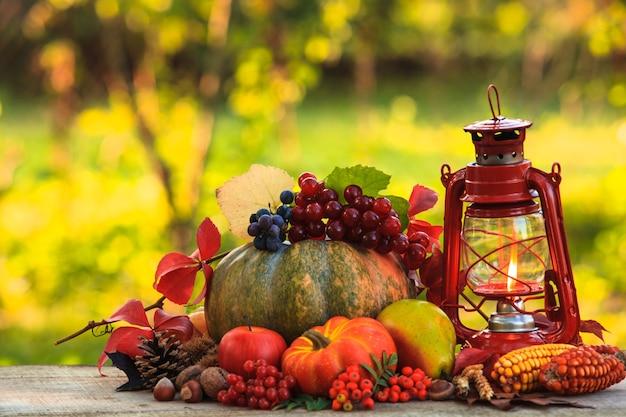 Frutta e noci, zucche sul tavolo all'aperto e lampada a cherosene - autunno accogliente