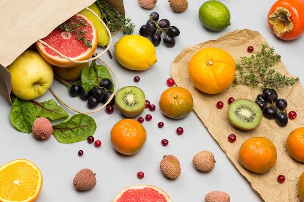 Frutta in sacchetto di carta. cachi, kiwi e arancia sul tavolo