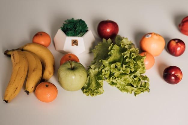 Frutta e verdura sono disposte su un tavolo bianco
