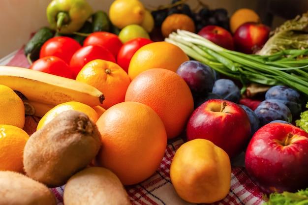 Frutta, verdura e verdure giacciono sul tavolo, luce naturale dalla finestra.