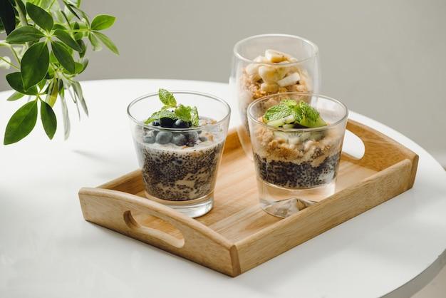 Parfait di yogurt alla frutta con muesli e semi di chia per una sana colazione su un tavolo di legno