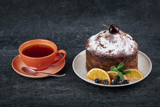Torta fruttata nel piatto con fette di arancia secca e una tazza di tè