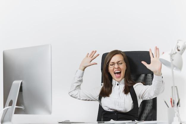 Donna d'affari arrabbiata frustrata seduta alla scrivania, lavorando al computer con documenti in ufficio leggero, imprecando e urlando, alzando le mani, copia spazio per la pubblicità