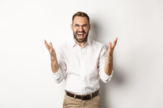 Uomo frustrato e arrabbiato che urla di rabbia, stringe la mano furioso, in piedi su sfondo bianco. copia spazio