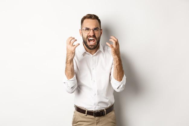Uomo frustrato e arrabbiato che urla di rabbia, stringe la mano furioso, in piedi su sfondo bianco.