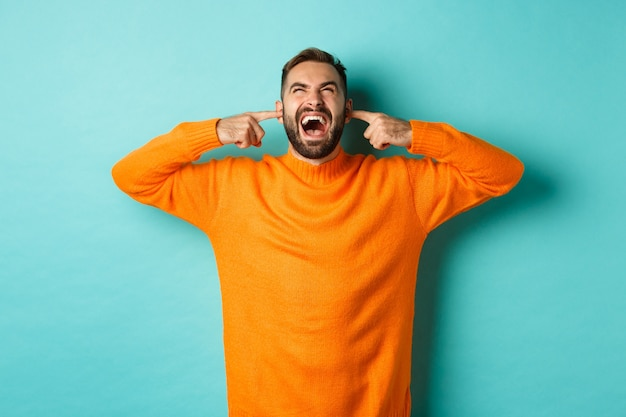 Uomo frustrato e infastidito che grida ai vicini al piano di sopra, orecchie chiuse con le dita, forte fastidio